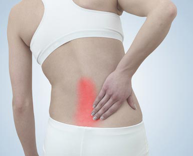 Acute lower back pain in a womans back. Female from behind holdi